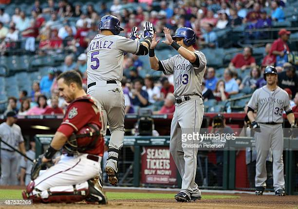 Carlos Gonzalez of the Colorado Rockies is congratulated by Drew Stubbs after Gonzalez hit a tworun home run against the Arizona Diamondbacks during...