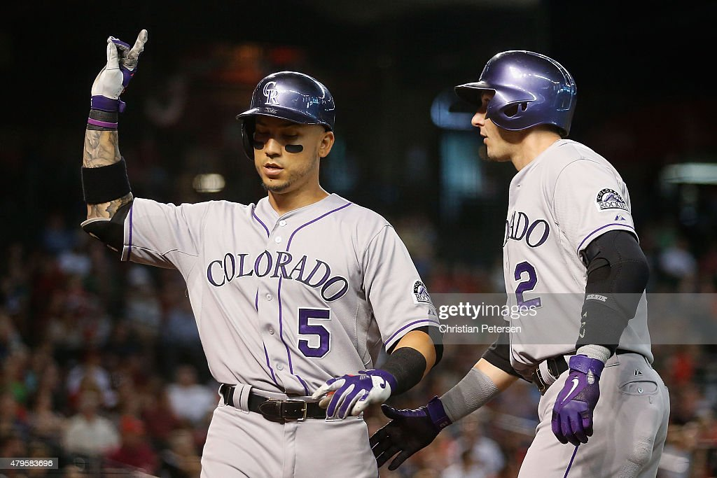 Carlos Gonzalez #5 of the Colorado Rockies is congratulated by Troy Tulowitzki #2 after Gonzalez hit a two run home-run against the Arizona Diamondbacks during the sixth inning of the MLB game at Chase Field on July 5, 2015 in Phoenix, Arizona.