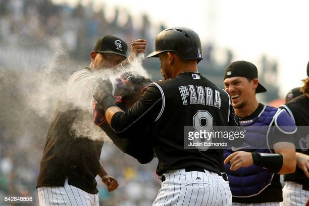 Carlos Gonzalez of the Colorado Rockies is doused with powder by a teammate as Gerardo Parra and catcher Tony Wolters join in the celebration after...