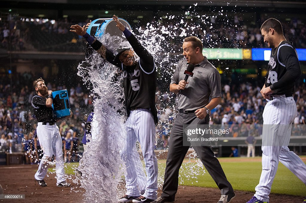 Carlos Gonzalez #5 of the Colorado Rockies is drenched by a teammate after hitting a walk-off 2-run home run to put the Rockies ahead of the Dodgers 8-6 at Coors Field on September 26, 2015 in Denver, Colorado.