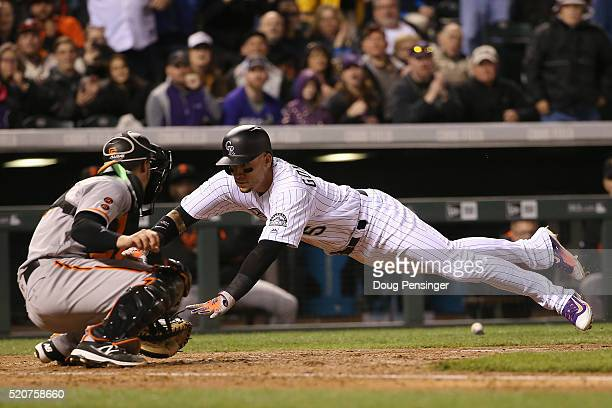 Carlos Gonzalez of the Colorado Rockies is tagged out at home plate by catcher Trevor Brown of the San Francisco Giants while tying to score on a...