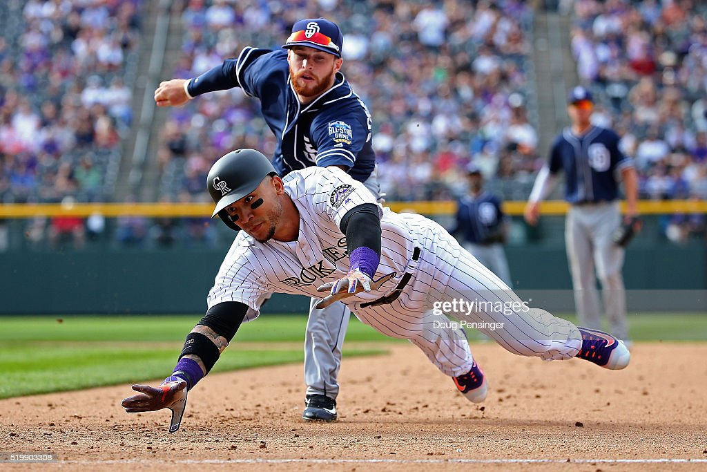 Carlos Gonzalez #5 of the Colorado Rockies is tagged out by second baseman Cory Spangenberg #15 of the San Diego Padres for a double play after getting caught in a rundown on a ground out by Gerardo Parra #8 of the Colorado Rockies in the seventh inning during opening day at Coors Field on April 8, 2016 in Denver, Colorado. The Padres defeated the Rockies 13-6.