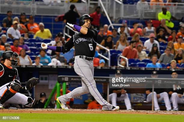 Carlos Gonzalez of the Colorado Rockies singles in the third inning during the game between the Miami Marlins and the Colorado Rockies at Marlins...