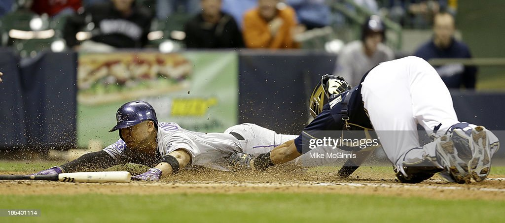 Carlos Gonzalez #5 of the Colorado Rockies slides head first into home plate while getting tagged out by Martin Maldonado #12 of the Milwaukee Brewers during the top of the eighth inning at Miller Park on April 3, 2013 in Milwaukee, Wisconsin.