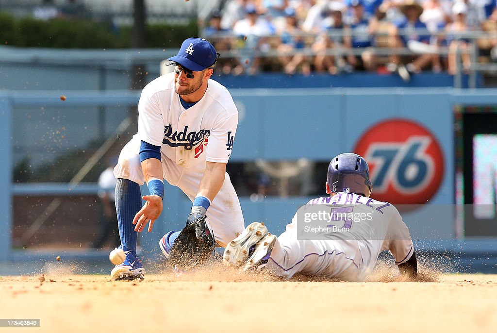 Carlos Gonzalez #5 of the Colorado Rockies slides into second with a stolen base head of the throw to second baseman Skip Schumaker #55 of the Los Angeles Dodgers in the ninth inning at Dodger Stadium on July 14, 2013 in Los Angeles, California. The Rockies won 3-1.