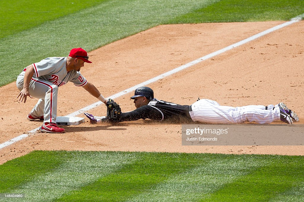 Carlos Gonzalez #5 of the Colorado Rockies slides into third base with an RBI triple just ahead of the tag by third baseman <a gi-track='captionPersonalityLinkClicked' href=/galleries/search?phrase=Placido+Polanco&family=editorial&specificpeople=213170 ng-click='$event.stopPropagation()'>Placido Polanco</a> #27 of the Philadelphia Phillies during the sixth inning at Coors Field on July 15, 2012 in Denver, Colorado. The Phillies defeated the Rockies 5-1.