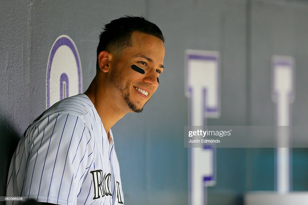 Carlos Gonzalez #5 of the Colorado Rockies smiles in the dugout during a game against the Cincinnati Reds at Coors Field on July 26, 2015 in Denver, Colorado. Gonzalez had two home runs to help the Rockies defeat the Reds 17-7.
