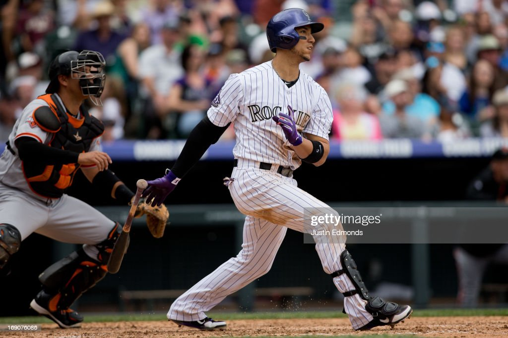 Carlos Gonzalez #5 of the Colorado Rockies watches his RBI double as catcher Guillermo Quiroz #12 of the San Francisco Giants looks on during the fifth inning at Coors Field on May 19, 2013 in Denver, Colorado. The Rockies defeated the Giants 5-0.