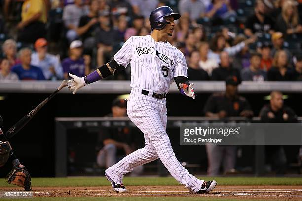 Carlos Gonzalez of the Colorado Rockies watches his solo home run off of starting pitcher Chris Heston of the San Francisco Giants to take a 10 lead...