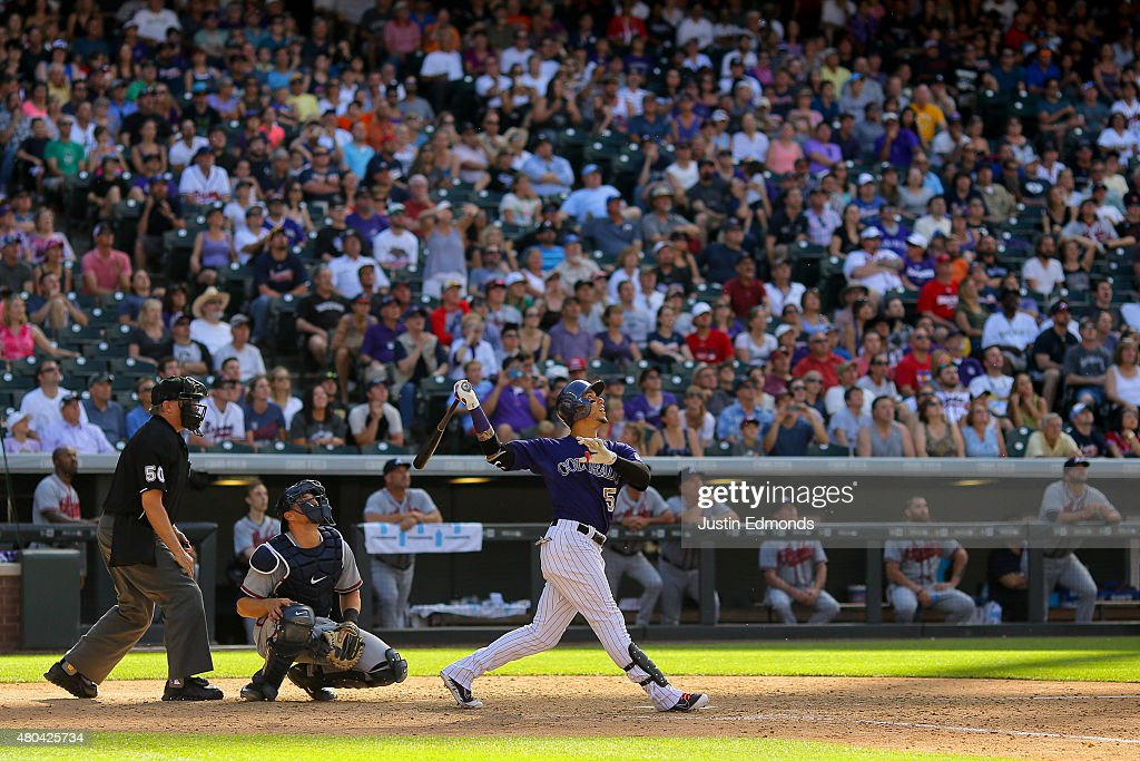 Carlos Gonzalez #5 of the Colorado Rockies watches his walk-off RBI single in the ninth inning as Ryan Lavarnway #30 of the Atlanta Braves and home plate umpire Paul Emmel look on at Coors Field on July 11, 2015 in Denver, Colorado. The Rockies defeated the Braves 3-2.