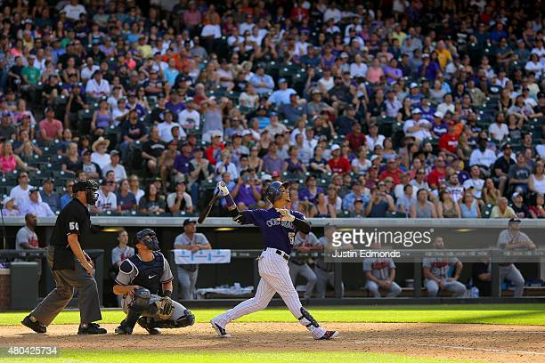 Carlos Gonzalez of the Colorado Rockies watches his walkoff RBI single in the ninth inning as Ryan Lavarnway of the Atlanta Braves and home plate...