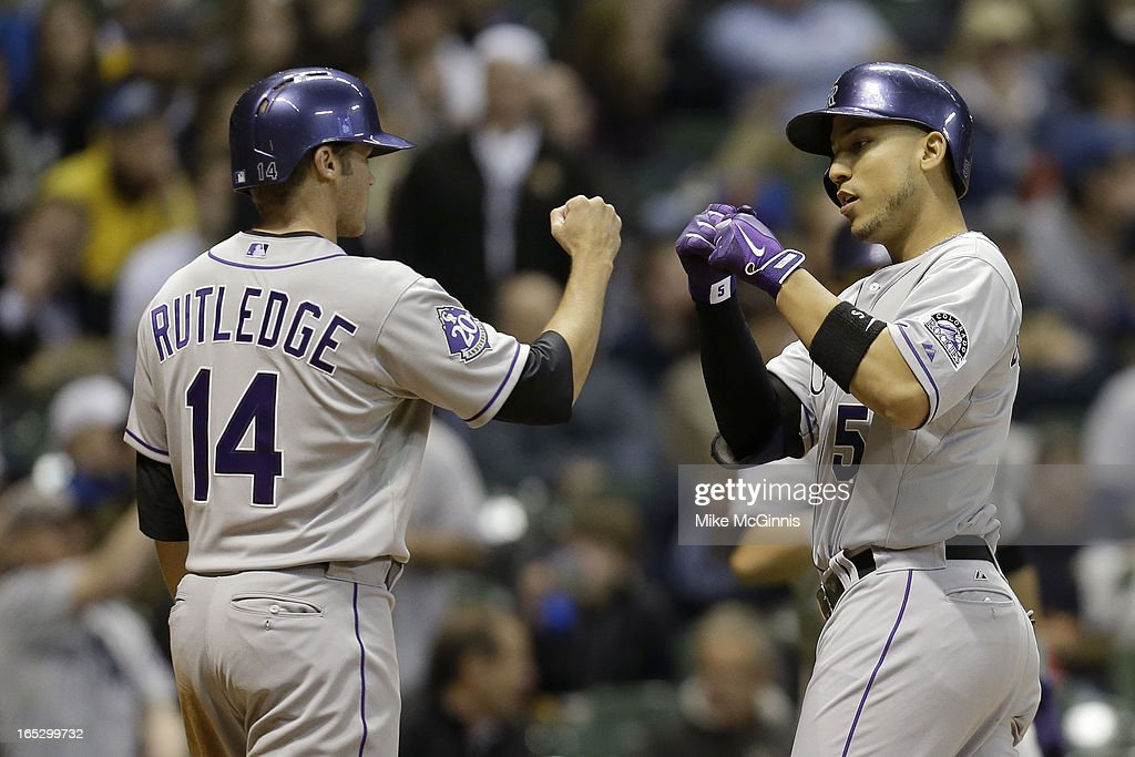 Carlos Gonzalez #5 of the Milwaukee Brewers celebrates with <a gi-track='captionPersonalityLinkClicked' href=/galleries/search?phrase=Josh+Rutledge&family=editorial&specificpeople=9541486 ng-click='$event.stopPropagation()'>Josh Rutledge</a> #14 after hitting a two-run homer in the top of the fifth inning against the Colorado Rockies at Miller Park on April 2, 2013 in Milwaukee, Wisconsin.