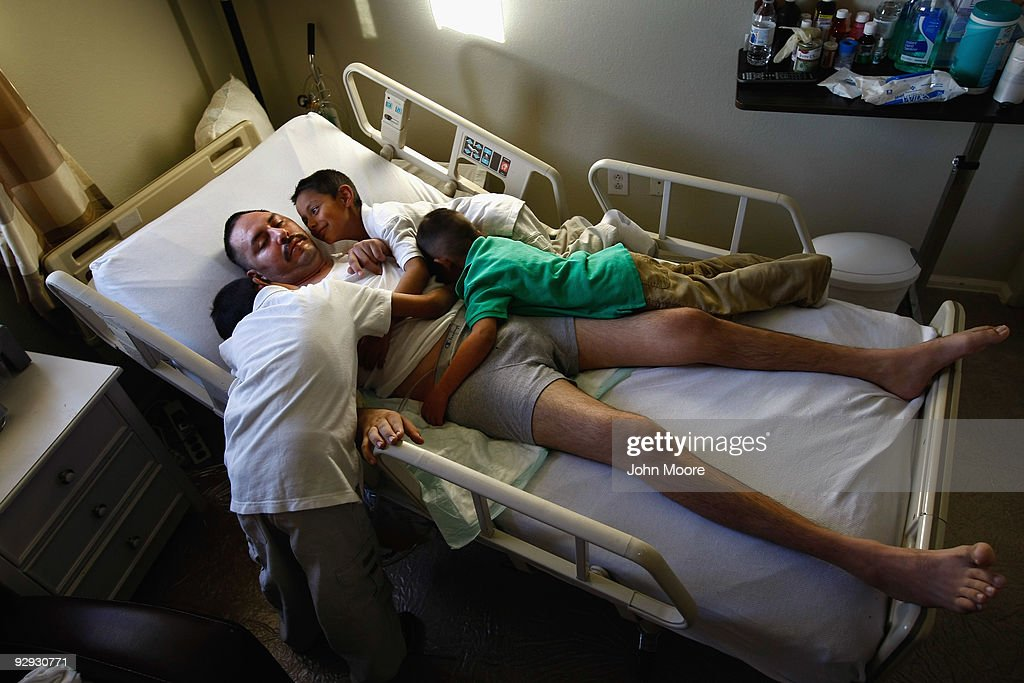 Carlos Granillo, 31, is embraced by his sons in his bed at home on November 9, 2009 in Denver, Colorado. Granillo, an immigrant from Mexico, suffered severe brain damage in a jet ski accident in July and received emergency medical care at a hospital emergency room. He was working as a construction worker without health insurance when the accident occurred. He receives home health care visits from Dominican Sisters Home Health Agency, a non-profit that performs some 25,000 home visits each year in the Denver area. The agency provides free home nursing care to patients with chronic diseases, helps them to better manage their disabling illnesses and provides custodial services with the aim of keeping patients in their homes and out of more expensive nursing home care.
