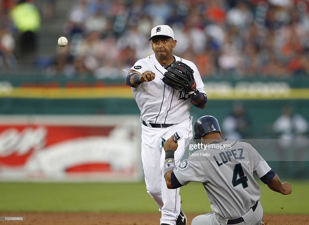 Carlos Guillen #9 of of the Detroit Tigers turns a double play forcing out Jose Lopez #4 of the Seattle Mariners at second base during the seventh inning of the game on July 2, 2010 at Comerica Park in Detroit, Michigan. The Tigers defeated the Mariners 7-1.