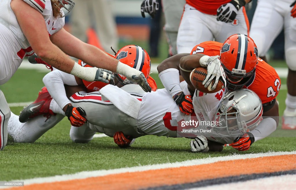 Carlos Hyde #34 of the Ohio State Buckeyes is stopped just short of the goal line by Ralph Cooper #42 and Earnest Thomas #9 of the Illinois Fighting Illini at Memorial Stadium on November 16, 2013 in Champaign, Illinois.