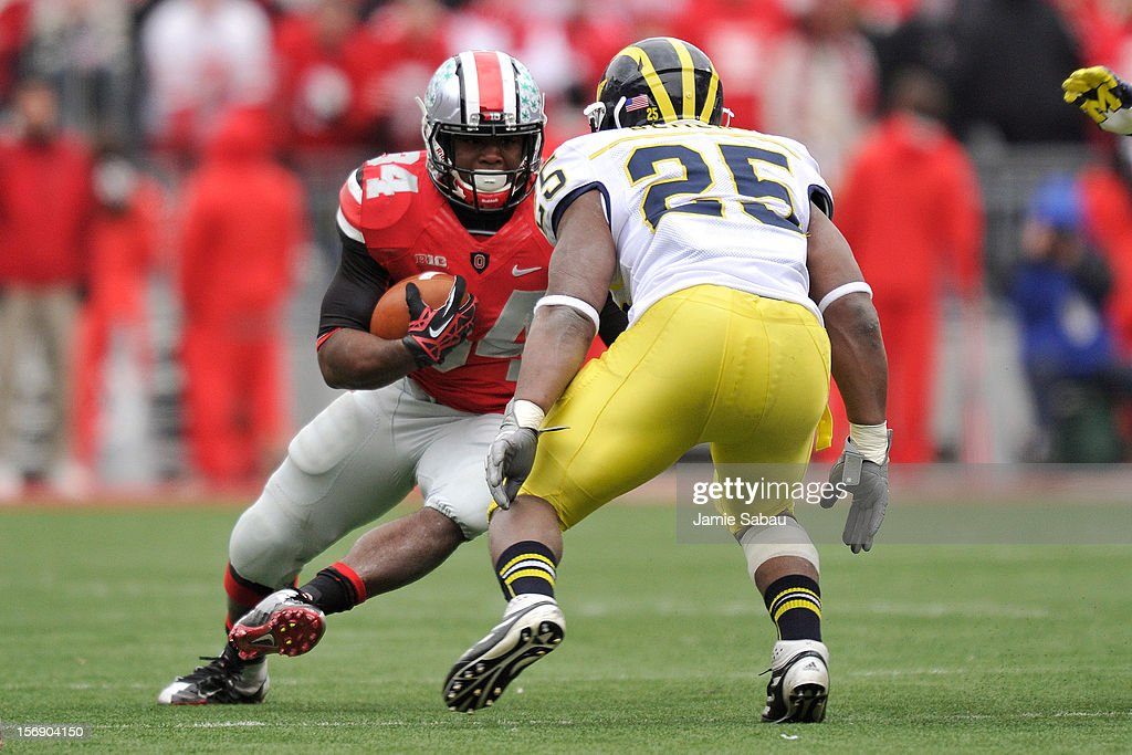 Carlos Hyde #34 of the Ohio State Buckeyes picks up yardage as Kenny Demens #25 of the Michigan Wolverines defends in the second half at Ohio Stadium on November 24, 2012 in Columbus, Ohio. Ohio State defeated Michigan 26-21.