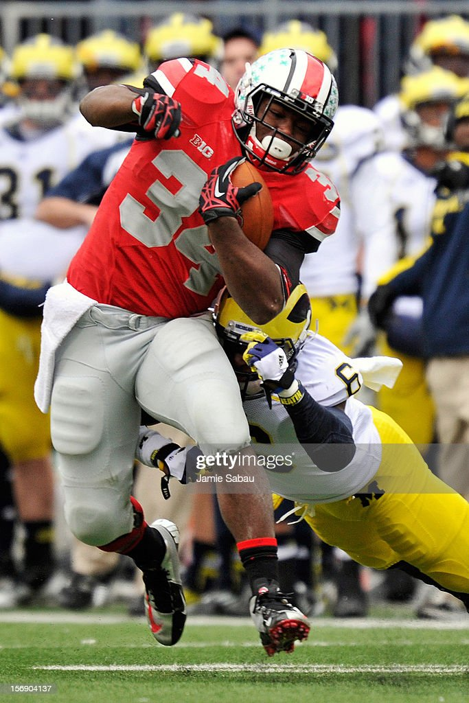 Carlos Hyde #34 of the Ohio State Buckeyes picks up yardage in the second half as Raymon Taylor #6 of the Michigan Wolverines attempts the tackle at Ohio Stadium on November 24, 2012 in Columbus, Ohio. Ohio State defeated Michigan 26-21.