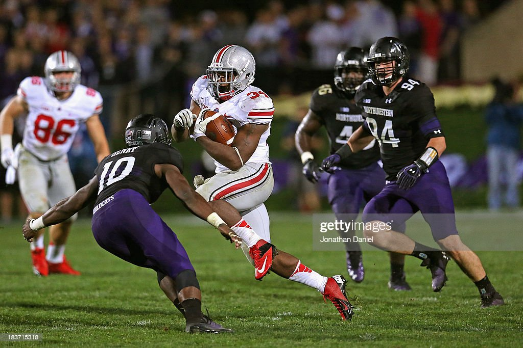 Carlos Hyde #34 of the Ohio State Buckeyes runs between Traveon Henry #10 and Dean Lowry #94 of the Northwestern Wilcats to score a second half touchdown at Ryan Field on October 5, 2013 in Evanston, Illinois. Ohio State defeated Northwestern 40-30.