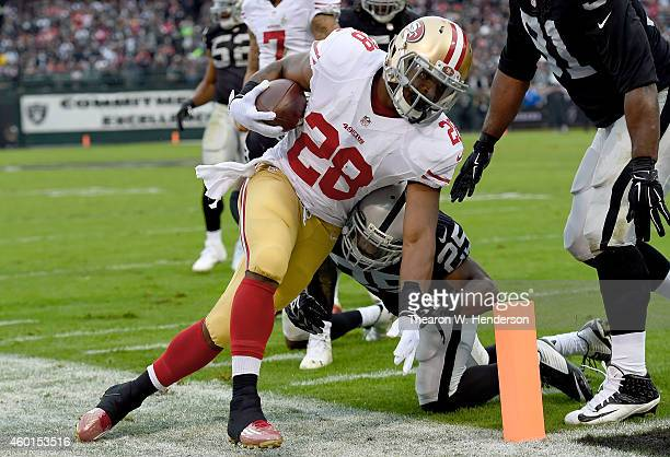 Carlos Hyde of the San Francisco 49ers gets tripped up and forced out of bounds by Brandian Ross of the Oakland Raiders in the second quarter at Oco...