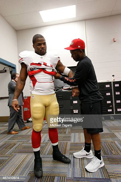Carlos Hyde of the San Francisco 49ers has help getting his pads on by Robert Lloyd the locker room prior to the game against the St Louis Rams at...