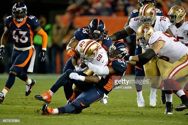 Carlos Hyde of the San Francisco 49ers is brought down by Brandon Marshall of the Denver Broncos and Nate Irving of the Denver Broncos in the third...