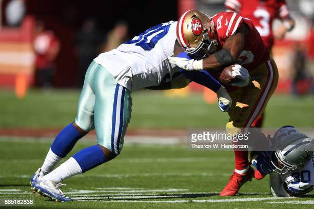 Carlos Hyde of the San Francisco 49ers is hit by DeMarcus Lawrence of the Dallas Cowboys during their NFL game at Levi's Stadium on October 22 2017...