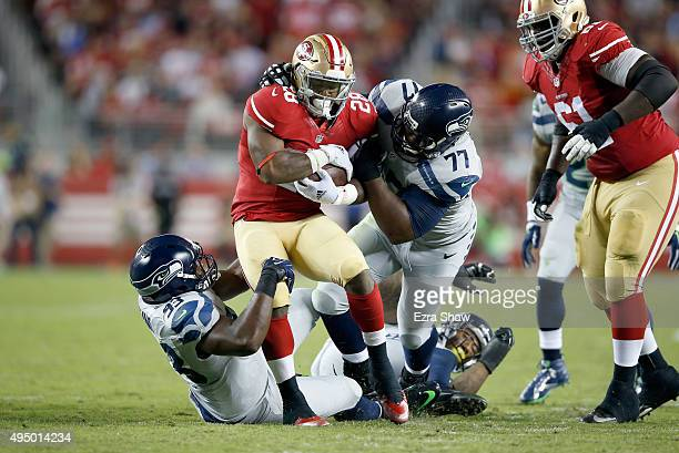 Carlos Hyde of the San Francisco 49ers is tackled by Ahtyba Rubin and David King of the Seattle Seahawks at Levi's Stadium on October 22 2015 in...