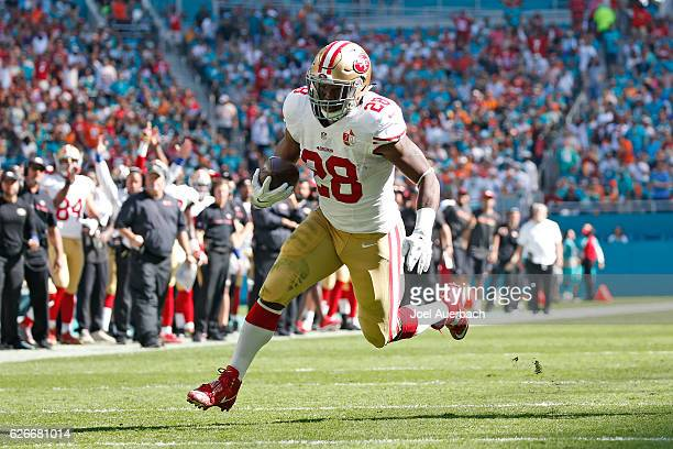 Carlos Hyde of the San Francisco 49ers runs for a first quarter touchdown against the Miami Dolphins on November 27 2016 at Hard Rock Stadium in...