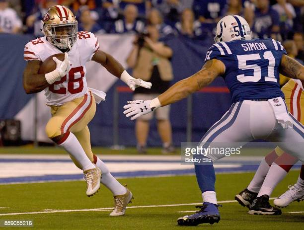 Carlos Hyde of the San Francisco 49ers runs past John Simon of the Indianapolis Colts during the first quarter of the game at Lucas Oil Stadium on...