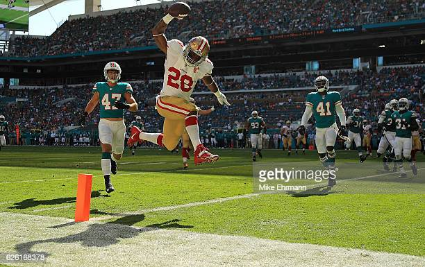 Carlos Hyde of the San Francisco 49ers scores a touchdown during a game against the Miami Dolphins on November 27 2016 in Miami Gardens Florida