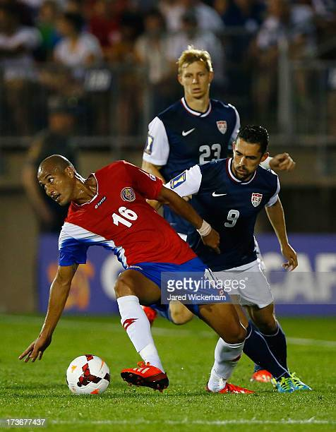 Carlos Johnson of Costa Rica carries the ball in front of Herculez Gomez of the United States during the CONCACAF Gold Cup match at Rentschler Field...