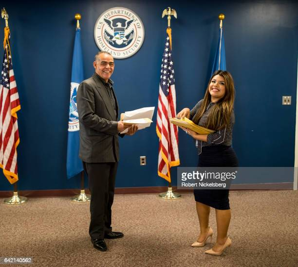 Carlos Jose Leonardo left receives his Certificate of Naturalization from a US government employee right during a naturalization ceremony for new US...