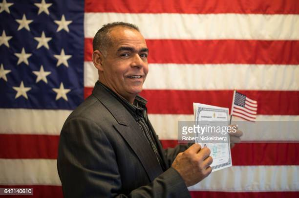 Carlos Jose Leonardo originally from the Dominican Republic stands for a picture holding his Certificate of Naturalization during a ceremony for new...