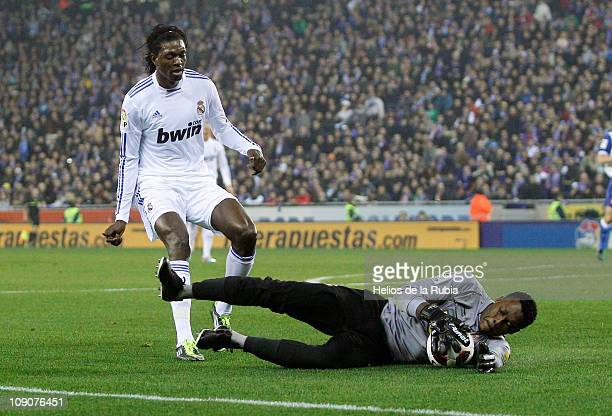 Carlos Kameni of Espanyol catches the ball beside Emmanuel Adebayor of Real Madrid during the La Liga match between Espanyol and Real Madrid at...