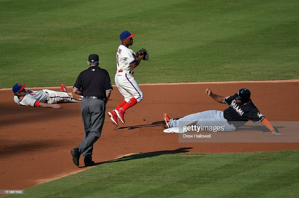 Carlos Lee #45 of the Miami Marlins is put out at second base by Jimmy Rollins #11 of the Philadelphia Phillies as Chase Utley #26 watches at Citizens Bank Park on September 12, 2012 in Philadelphia, Pennsylvania.