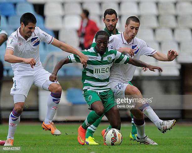 Carlos Mane of Sporting Clube de Portugal is tackled by Jose Aja of Club Nacional de Football during the Teresa Herrera Trophy match between Sporting...