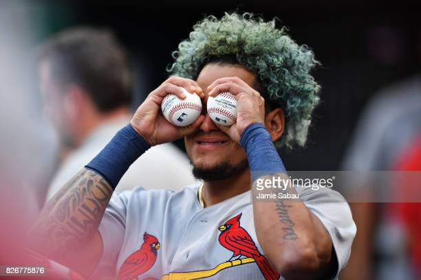 Carlos Martinez of the St Louis Cardinals turns a pair of baseballs into binoculars in the dugout during the second inning against the Cincinnati...