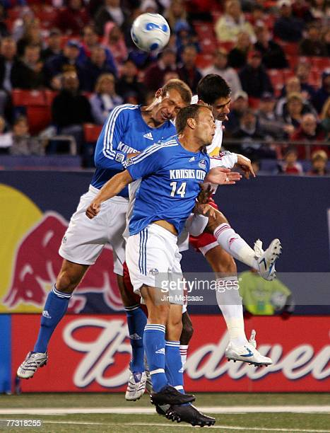 Carlos Mendes of the New York Red Bulls goes up for a header against Jimmy Conrad and Jack Jewsbury of the Kansas City Wizards on October 13 2007 at...
