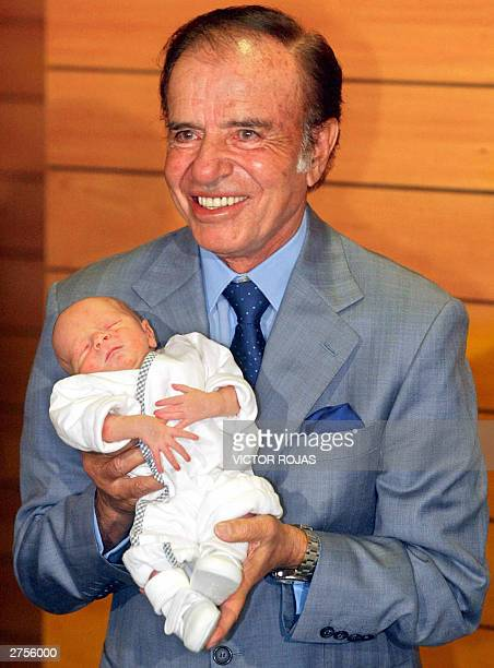 Carlos Menem a controversial figure as Argentina's president from 19891999 holds Maximo Saul his son with Chileanborn wife former beauty queen...