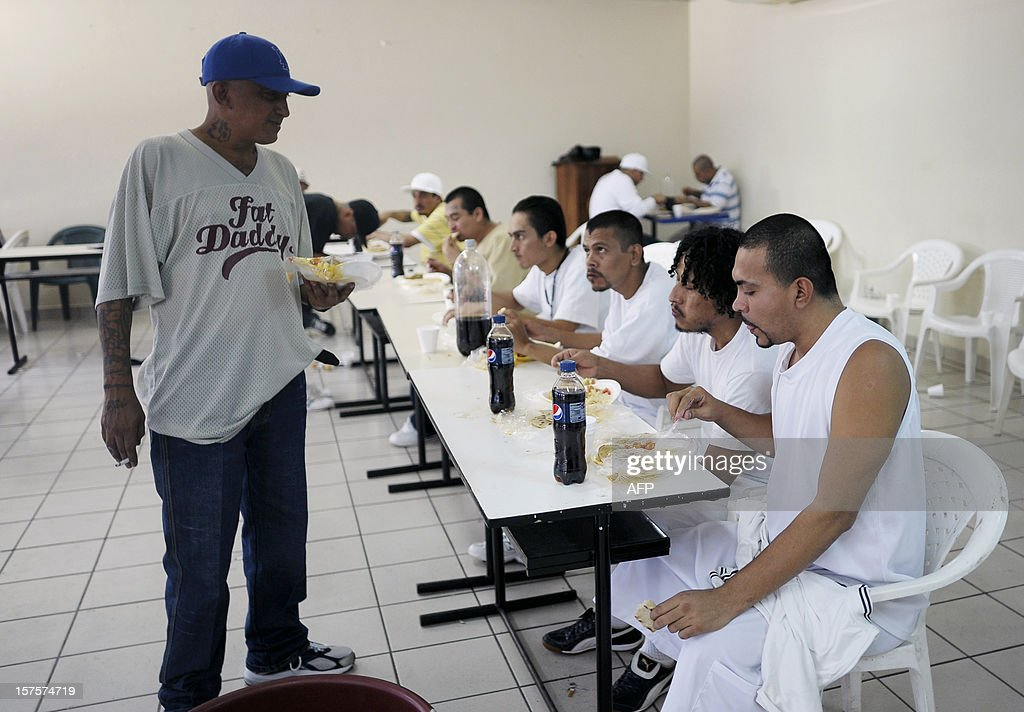 Carlos Mojica Lechuga (L), leader of the Mara 18, speaks with inmates after a press conference with both Mara 18 and Mara Salvatrucha members and Salvadorean government mediators, at La Esperanza jail in San Salvador, El Salvador on December 4, 2012. Gang members announced their proposal to create sanctuary territories for gangs as a part of the truce started earlier this year. AFP PHOTO/Jose CABEZAS