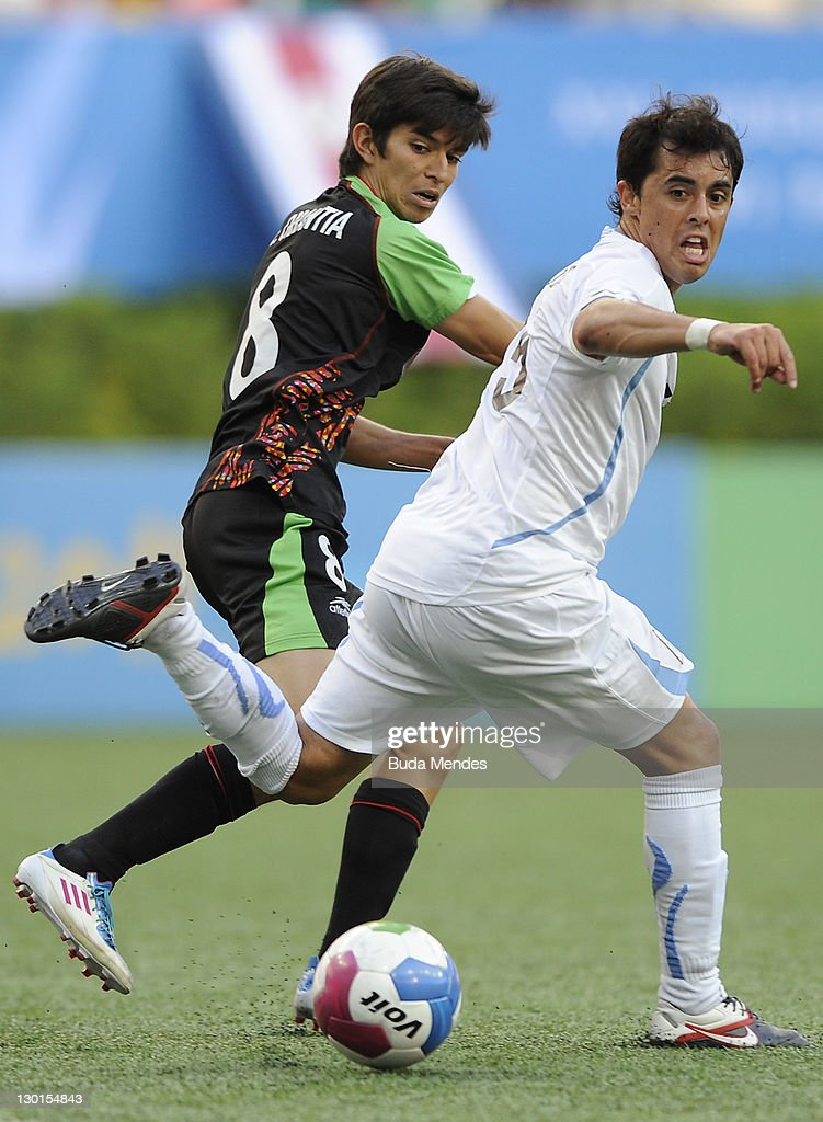 Carlos Orrantia of Mexico struggles for the ball with Gaston Silva of Uruguay during a match as part of XVI Pan American Games at Omnilife stadium on October 23, 2011 in Guadalajara, Mexico.