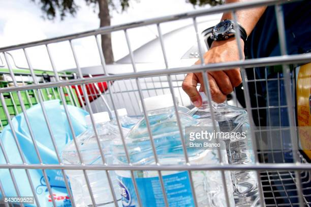 Carlos Otero of St Petersburg loads his car with water bottles outside of a Publix grocery store as residents in the area prepare ahead of Hurricane...