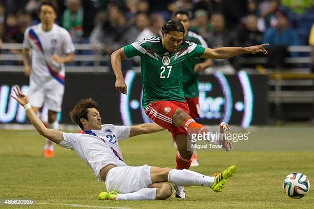 Carlos Peñ–a of Mexico fights for the ball with Park JongWoo of Korea during a FIFA friendly match between Mexico and South Korea at Alamodome...