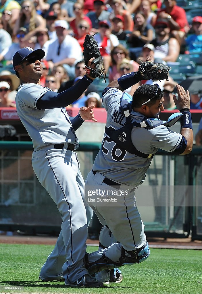 Carlos Pena #23 and <a gi-track='captionPersonalityLinkClicked' href=/galleries/search?phrase=Jose+Molina&family=editorial&specificpeople=206365 ng-click='$event.stopPropagation()'>Jose Molina</a> #28 of the Tampa Bay Rays collide while trying to catch a foul ball in the fifth inning against the Los Angeles Angels of Anaheim at Angel Stadium of Anaheim on August 19, 2012 in Anaheim, California.