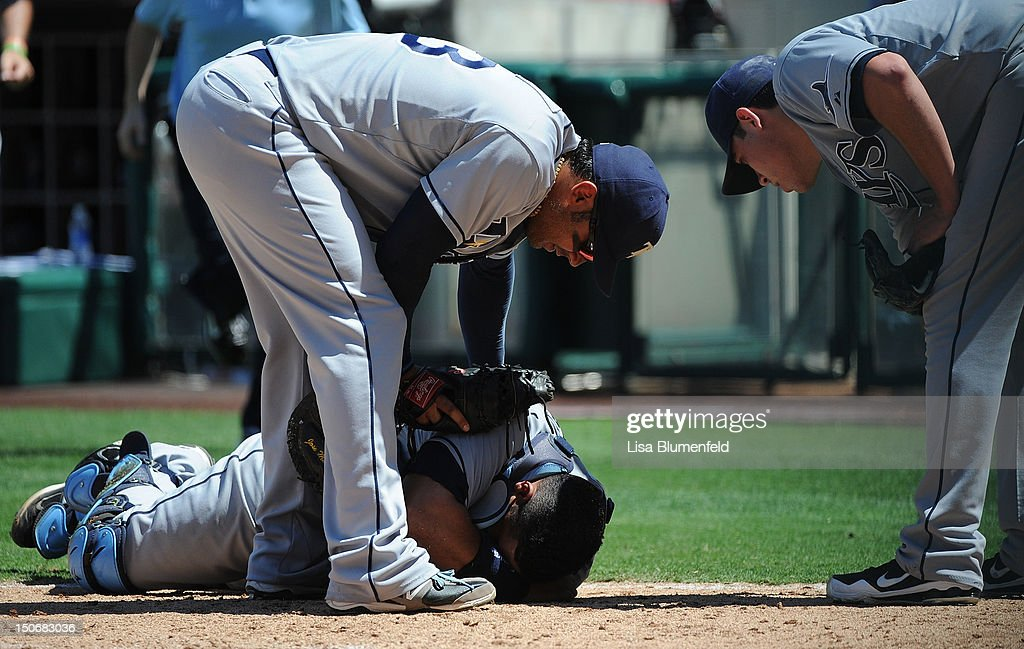 Carlos Pena #23 (L) and <a gi-track='captionPersonalityLinkClicked' href=/galleries/search?phrase=Matt+Moore+-+Baseball+Player&family=editorial&specificpeople=15003307 ng-click='$event.stopPropagation()'>Matt Moore</a> #23 (R) of the Tampa Bay Rays tend to teammate <a gi-track='captionPersonalityLinkClicked' href=/galleries/search?phrase=Jose+Molina&family=editorial&specificpeople=206365 ng-click='$event.stopPropagation()'>Jose Molina</a> #28 in the fifth inning against the Los Angeles Angels of Anaheim at Angel Stadium of Anaheim on August 19, 2012 in Anaheim, California.