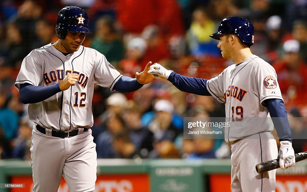 Carlos Pena #12 is congratulated by teammate Robbie Grossman #19 of the Houston Astros after scoring against the Boston Red Sox during the game on April 27, 2013 at Fenway Park in Boston, Massachusetts.
