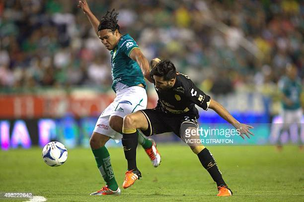 Carlos Pena of Leon vies for the ball with Nestor Vidrio of Dorados during their Mexican Apertura tournament football match at the Nou Camp stadium...