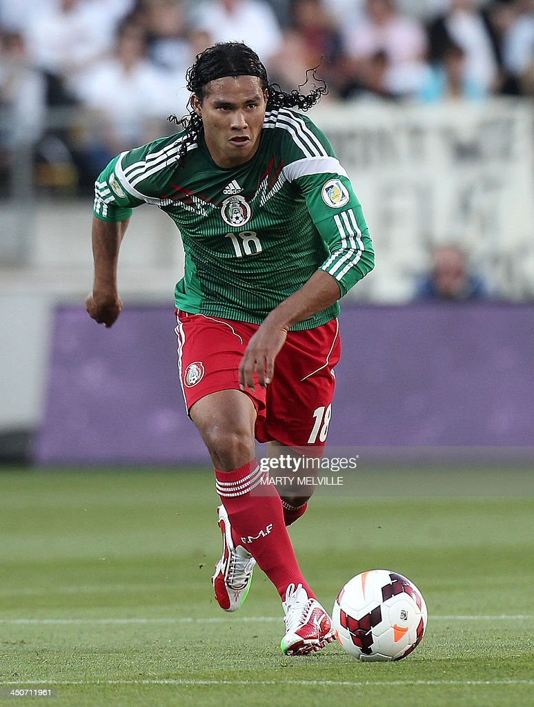 Carlos Pena of Mexico dribbles the ball against New Zealand in their World Cup qualifying football match in Wellington on November 20, 2013. Mexico won 4-2. AFP PHOTO / MARTY MELVILLE