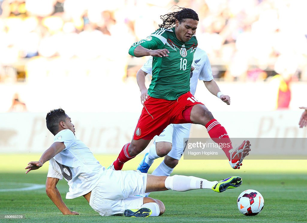 Carlos Pena of Mexico evades the tackle of Bill Tuiloma of New Zealand during leg 2 of the FIFA World Cup Qualifier match between the New Zealand All Whites and Mexico at Westpac Stadium on November 20, 2013 in Wellington, New Zealand.