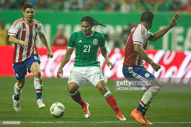 Carlos Pena of Mexico vies for the ball with Luis Neri Caballero and William Da Silva of Paraguay during the friendly match between the Mexican...